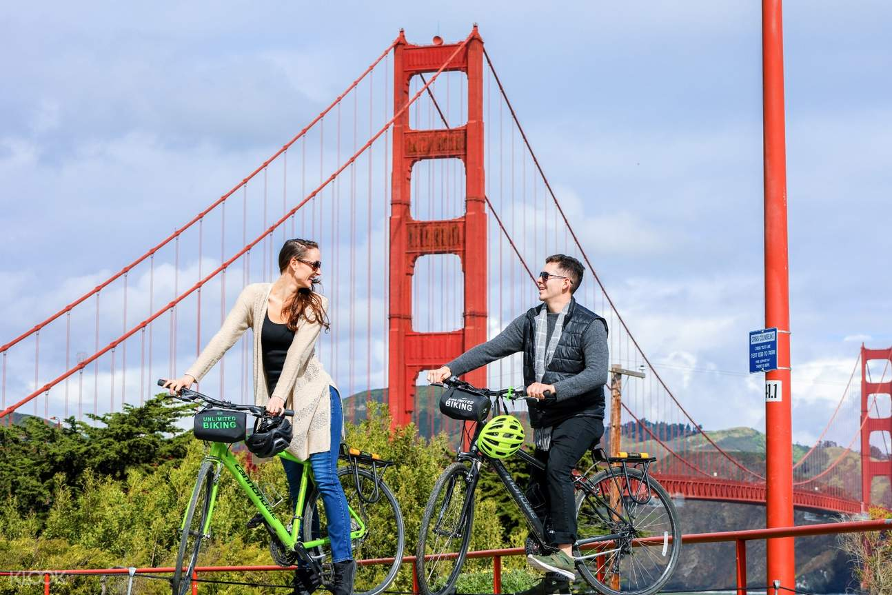 a couple riding bikes near the Golden Gate Bridge